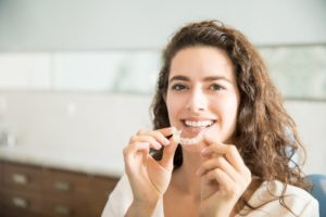 person holding clear aligners